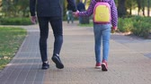 supervise : Father walking with daughter to school, holding hand, caring about child safety
