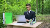 kifinomult : Serious businessman in suit working on laptop at office desk in forest fresh air