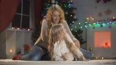 milagre : Cheerful lady and girl having fun under glowing Christmas tree family traditions Stock Footage