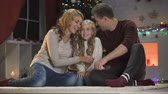 papai noel : Cute little girl telling happy parents X-mas wish, they hugging her and smiling