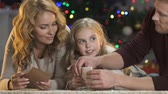 papai noel : Happy parents helping cute girl with letter to Santa Claus. Vídeos