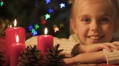 advento : Girl looking at burning candles, happy childhood and faith in Christmas miracle Stock Footage