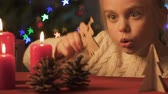 delighted : Girl playing with pine cones and wooden Christmas toys, festive atmosphere Stock Footage