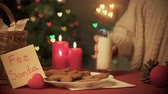 presentes : Girl putting glass of milk for Santa near burning candles and honey cookies Vídeos