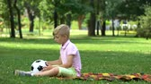 juffrouw : Sad boy sitting in park and throwing ball, lack of friends, victim of bullying