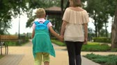 tragédia : Mother and child walking home after classes, son talking about day at school Stock Footage
