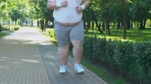 trotting : Fat man with big belly running in park early in morning, desire to lose weight