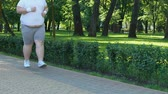 trotting : Young pot-bellied guy running outdoors, struggling with insecurities, dieting