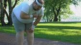 ischemic : Obese man feeling sharp pain in chest during jogging, lady helps him, problems