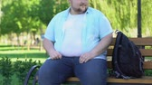 overcome : Funny chubby male sitting on bench in park and curiously looking at passersby
