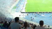 videospiel : Soccer fans watching game, film crews and guards stand around football pitch Videos