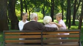 vnuk : Cute siblings running to grandparents sitting on bench in public park, family