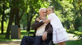 ответственность : Cute girl hugging grandfather sitting in wheelchair, walk in park, pastime Стоковые видеозаписи