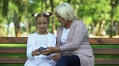 разрыв : Cute granddaughter teaching granny how to use modern smartphone, generation gap