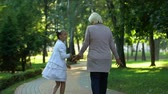 쾌적한 : Excited girl telling grandmother stories during walk in park having fun. 무비클립