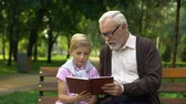 vnuk : Grandpa teaches grandson to read book, encourages boy to knowledge, education