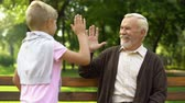 educação : Grandpa gives high-five to grandson, friendship with boy and his upbringing