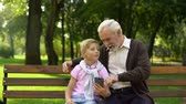 внук : Boy showing smartphone to happy grandfather, easy application for old people
