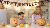 scaring : Mother showing carved jack-o-lantern to daughter and suddenly scaring her, fun