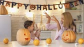 scaring : Funny mother scaring her little daughter preparing pumpkin for All Hallows Eve