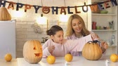 scaring : Little daughter putting toy spider on carved pumpkin, giving high five to mother