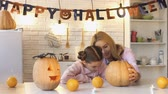 horror : Cute girl drawing scary face on pumpkin preparing for Halloween.
