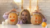 scaring : Funny mom hiding under table with carved pumpkins, scaring her family, pranks Stock Footage