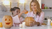 scaring : Daughter and mother carving pumpkin Jack-o-Lantern, spending time together