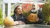 ухмыляясь : Daughter brings pumpkin jack-o-lantern to mother, preparation for Halloween