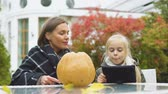 aplicativo : Mother carving pumpkin while daughter looking for tips in internet, blogging