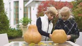 bratr : Children carving pumpkin Jack for Halloween party, boy helps girl with crafts