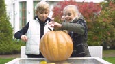 calabaza : Children carving pumpkin jack-o-lantern, excited with process, happy emotions Archivo de Video