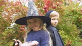 vyděsit : Girl in witch costume and boy-vampire posing for camera, Halloween celebration