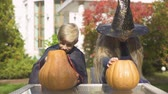 vampiro : Children in masquerade costumes carving pumpkin jack-o-lantern for Halloween