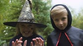 vyděsit : Girl in witch hat and boy in mantle chasing camera, growling spooky, Halloween