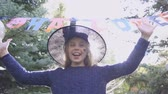 hurafe : Playful girl in witch hat standing at entrance to Halloween party, fun and jokes