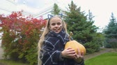 pléd : Cheerful girl shows thumb up, holds Jack pumpkin for Halloween, autumn holiday
