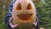 ухмыляясь : Girl demonstrating pumpkin Jack at camera, preparing for autumn Halloween party