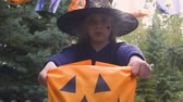 procura : Naughty girl in witch costume demanding sweets, trick or treat Halloween game