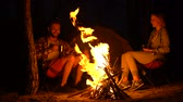 estilos de vida : Two campers warming up near campfire, telling funny stories, wild fire risk