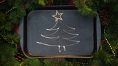 stopmotion : Wooden star-shape tree topper decorating drew with cream on oven tray xmas tree Stock Footage