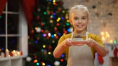 magdalenas : Adorable girl showing muffin at camera and smiling, happy Xmas atmosphere