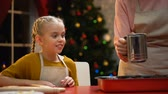 сочельник : Excited girl looking at granny powdering traditional Xmas muffins with sugar
