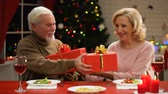 прочный : Aging couple exchanging presents on Christmas eve tender relations through years