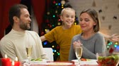 scaring : Girl jumping under table and scaring parents, all laughing and hugging, Xmas eve Stock Footage