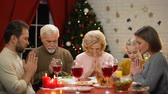 сочельник : Big family having traditional Xmas dinner, decorations sparkling on background Стоковые видеозаписи