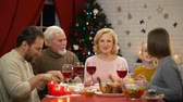 sylwester : Happy family having tasty healthy Xmas dinner together lights on tree glittering Wideo