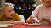 peperkoek : Granny teaching granddaughter to decorate gingerbread cookies with icing sugar