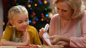 peperkoek : Child helping grandmother to decorate gingerbread cookies, homemade pastries