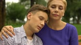 apathetic : Young son in despair putting head on mothers shoulder feeling calmness and love